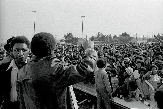Chico Neblett and Bobby Seale (back) leading audience with a Black Power salute at the Black Community Survival Conference, March 30, 1972 (Bob Fitch Photography Archive, Stanford University Libraries)